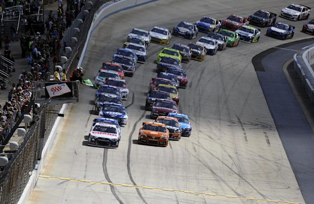 Dale Earnhardt Jr., left, Matt Kenseth, right, and others take the green flag to start a NASCAR Sprint Cup Series auto race on Sunday, Sept. 29, 2013, at Dover International Speedway in Dover, Del. (AP Photo/Nick Wass)
