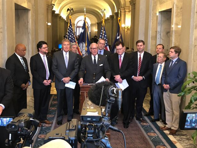 <p> South Carolina Gov. Henry McMaster stands with several legislators to talk about the states efforts to get the Carolina Panthers a new practice facility, Wednesday, March 13, 2019, in Columbia, S.C. Lawmakers will try to pass a bill making football players full-time workers under state law so the Panthers could get t tax credits. (AP Photo/Jeffrey Collins) </p>
