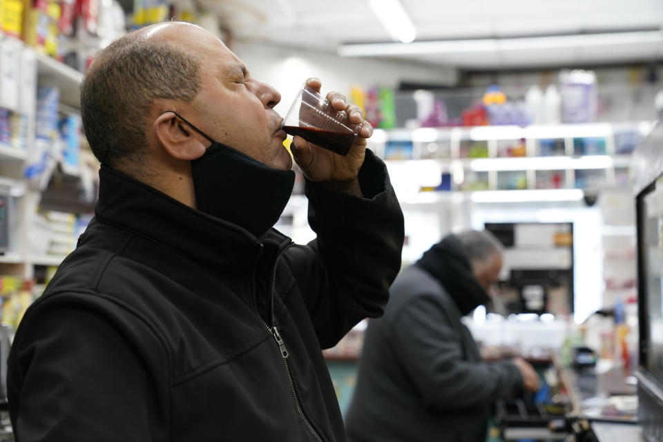 Bronx bodega owner Francisco Marte winces as he sips a homemade concoction containing garlic, carrots, beets, onion and ginger and other ingredients that he hopes will improve his immune system while he waits for the opportunity to get a COVID-19 vaccination, Wednesday, Feb. 10, 2021, at his store in the Bronx borough of New York. Marte, who heads up the Bodega and Small Business Group, which represents bodegas in New York, lobbied local officials to set aside vaccine appointments for bodega workers, many of whom are unaware they are eligible. He hopes the recent opening of a large vaccination site at Yankee stadium will make access easier for people like him. (AP Photo/Kathy Willens)