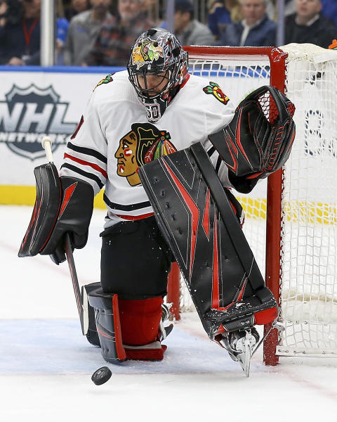 Chicago Blackhawks goaltender Corey Crawford (50) deflects the puck during the second period of an NHL hockey game against the St. Louis Blues Tuesday Feb. 25, 2020, in St. Louis. (AP Photo/Scott Kane)