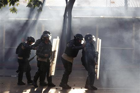 Riot police is seen among tear gas as they fight against students during a protest against President Nicolas Maduro's government in Caracas February 15, 2014. REUTERS/Carlos Garcia Rawlins