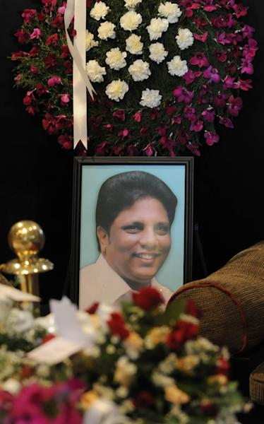 A photo of the slain editor of Sri Lanka's Sunday Leader Newspaper Lasantha Wickrematunga surrounded by floral tributes during a funeral ceremony at his home in Colombo ahead of the burial on January 12, 2009 (AFP Photo/Ishara S. Kodikara)