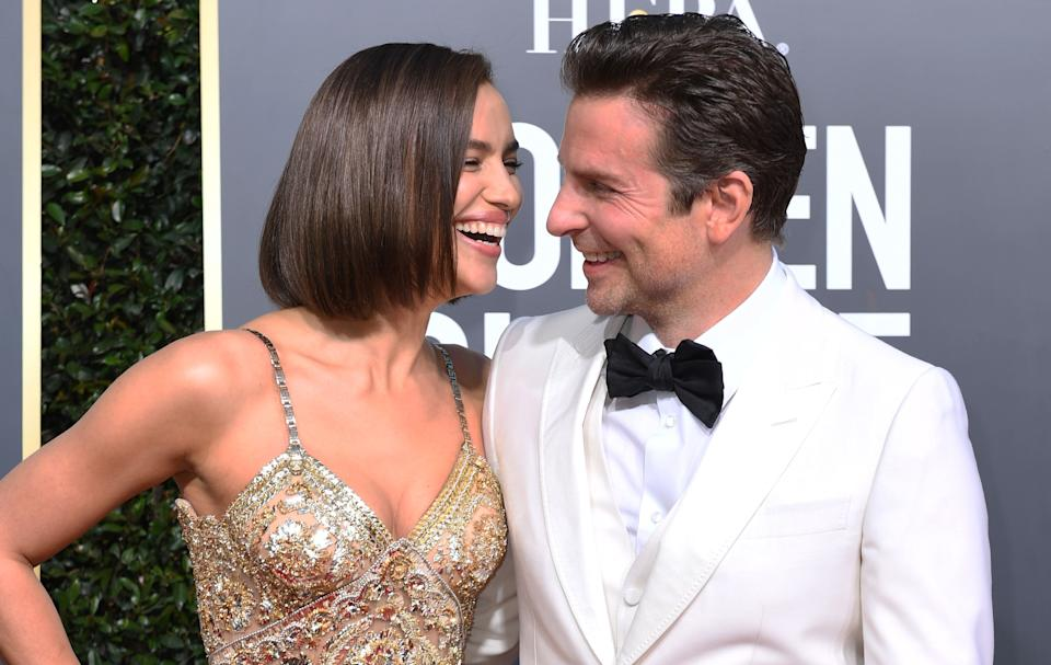 """TOPSHOT - Best Actor in a Motion Picture  Drama and Best Director  Motion Picture for """"A Star is Born"""" nominee Bradley Cooper (R) and his partner Russian model Irina Shayk arrive for the 76th annual Golden Globe Awards on January 6, 2019, at the Beverly Hilton hotel in Beverly Hills, California. (Photo by VALERIE MACON / AFP)        (Photo credit should read VALERIE MACON/AFP/Getty Images)"""