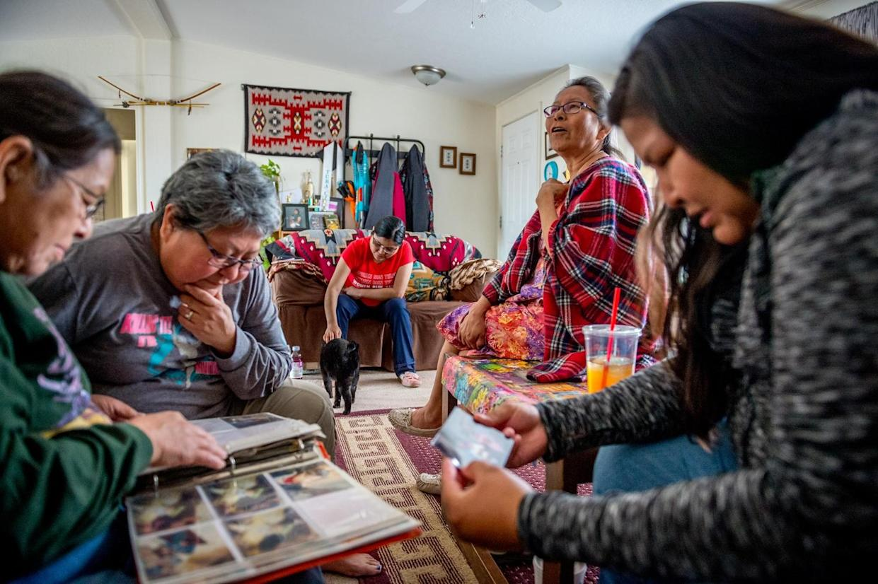 Linda Talker, Leona Begishie, Tara Begay and Carol Talker are pictured looking at family photo albums at their family home in Cameron, AZ. (Photograph by Mary F. Calvert)
