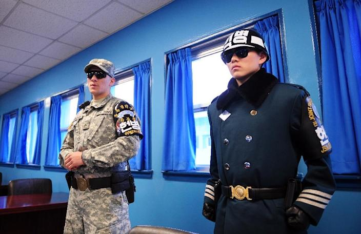 US (L) and South Korean (R) soldiers stand guard inside the UN conference room at the truce village of Panmunjom in the Demilitarised Zone dividing the two Koreas on March 12, 2014 (AFP Photo/Jung Yeon-Je)