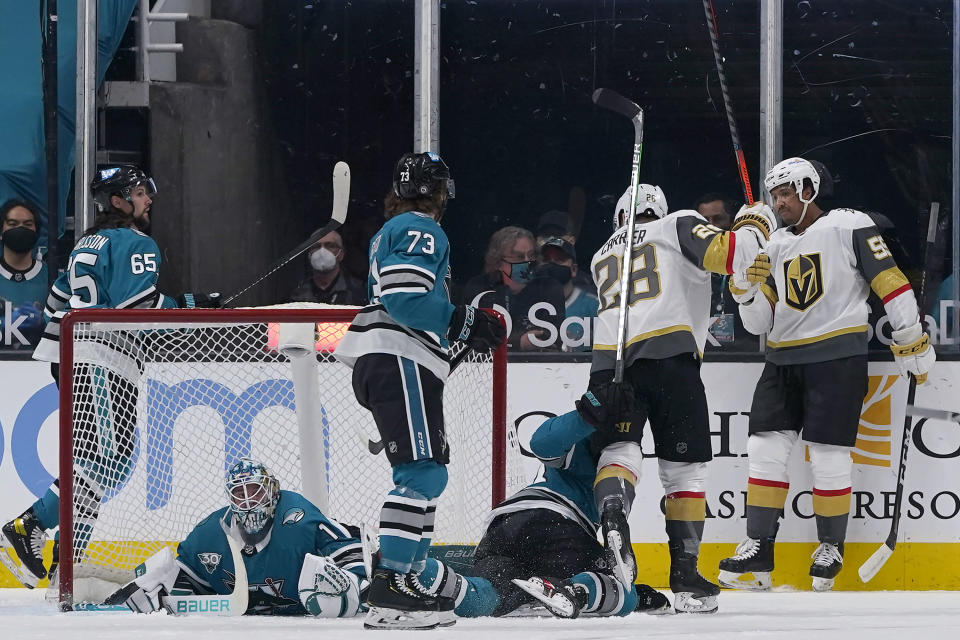 Vegas Golden Knights right wing Keegan Kolesar, right, is congratulated by left wing William Carrier (28) after scoring against San Jose Sharks goaltender Alexei Melnichuk, bottom left, during the first period of an NHL hockey game in San Jose, Calif., Wednesday, May 12, 2021. (AP Photo/Jeff Chiu)