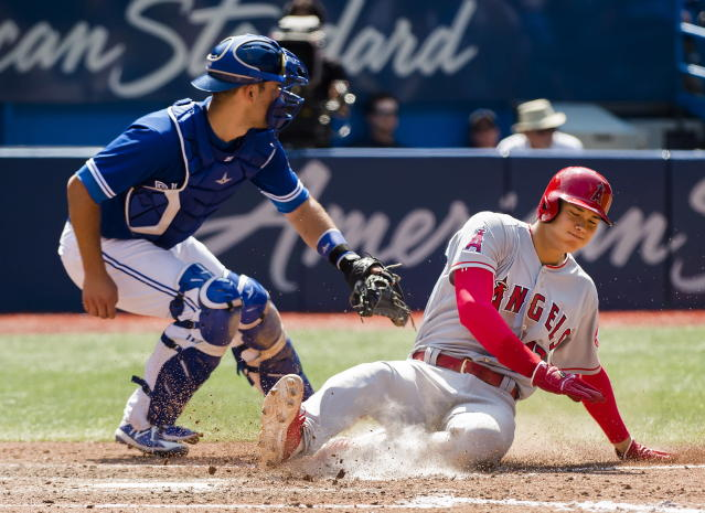 Los Angeles Angels designated hitter Shohei Ohtani (17) scores as he slides safe past Toronto Blue Jays catcher Luke Maile (21) during the ninth inning of a baseball game, Thursday, May 24, 2018 in Toronto. (Nathan Denette/The Canadian Press via AP)