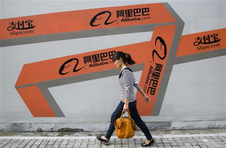 A woman walks past an Alibaba advertisement on a wall in Hangzhou
