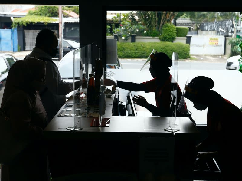 Workers wearing face shields and protective masks serve customers at the restaurant, in Jakarta