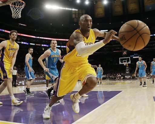 Los Angeles Lakers guard Kobe Bryant (24) chases a loose ball against the New Orleans Hornets in the first half of an NBA basketball game in Los Angeles Tuesday, April 9, 2013. (AP Photo/Reed Saxon)