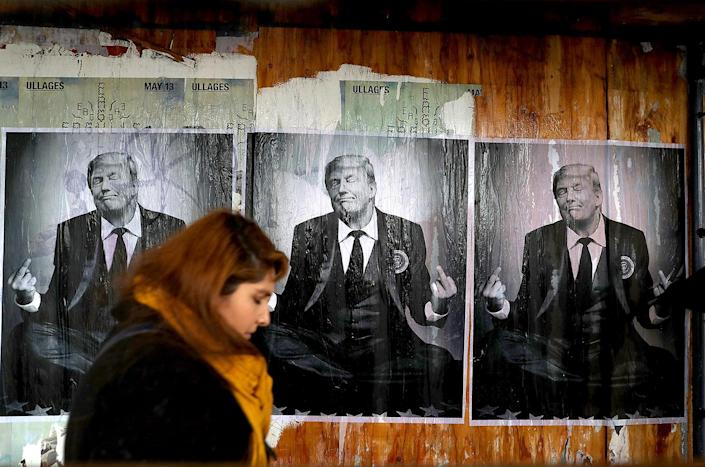 <p>A pedestrian walks past posters of President Donald Trump on Jan. 20, 2017 in Los Angeles. (Photo: Justin Sullivan/Getty Images) </p>