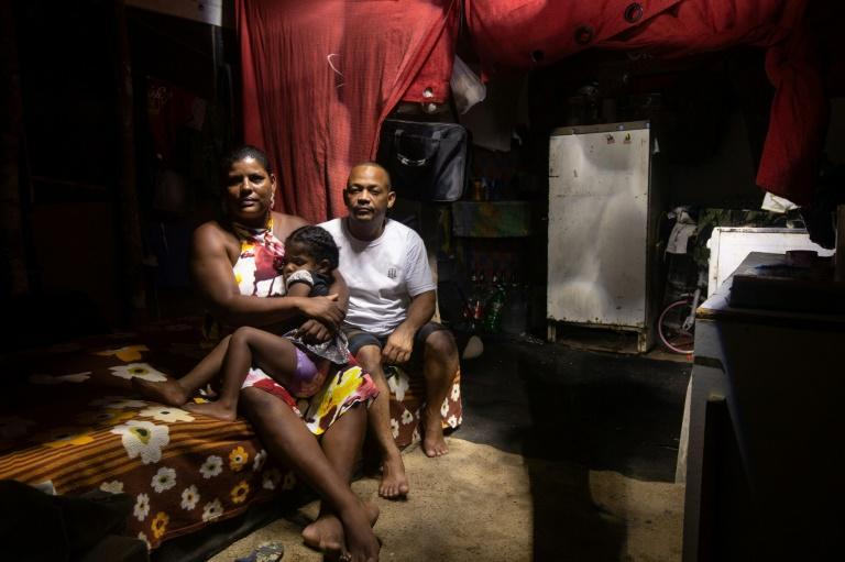 Ilma Silva Santos sits with her husband Antonio Pedro de Souza, a painter who has been out of work since the beginning of the pandemic, and one of their children in their shack in the Manuel Faustino squatter camp in Brazil