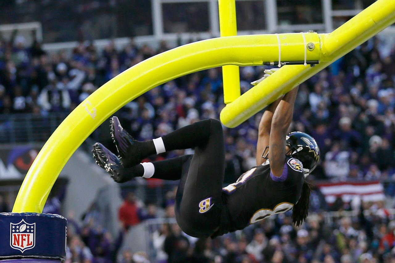 BALTIMORE, MD - DECEMBER 23:  Wide receiver Torrey Smith #82 of the Baltimore Ravens hangs on the goal post after catching a touchdown pass during the first quarter against the New York Giants at M&T Bank Stadium on December 23, 2012 in Baltimore, Maryland.  (Photo by Rob Carr/Getty Images)