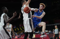 Italy's Niccolo Mannion, right, passes the ball past Germany's Johannes Voigtmann (7) during men's basketball preliminary round game at the 2020 Summer Olympics, Sunday, July 25, 2021, in Saitama, Japan. (AP Photo/Eric Gay)