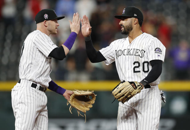 Colorado Rockies shortstop Trevor Story, left, congratulates left fielder Ian Desmond after the team's 2-1 win over the St. Louis Cardinals in a baseball game Wednesday, Sept. 11, 2019, in Denver. (AP Photo/David Zalubowski)