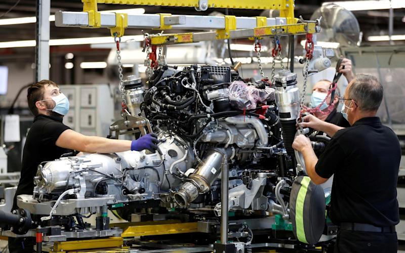 Technicians work on a Rolls-Royce engine prior to it being installed in a car on the production line of the Rolls-Royce Goodwood factory, near Chichester