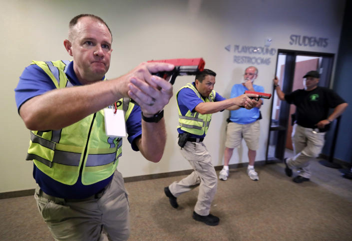 In this July 21, 2019 photo, Police officers David Riggall, left, and Nick Guadarrama, center, demonstrate to students Stephen Hatherley, center rear, and Chris Scott, right rear, how to clear a hallway intersection during a security training session at Fellowship of the Parks campus in Haslet, Texas. While recent mass shootings occurred at a retail store in El Paso, Texas, and a downtown entertainment district in Dayton, Ohio, they were still felt in houses of worship, which haven't been immune to such attacks. And some churches have started protecting themselves with guns. (AP Photo/Tony Gutierrez)