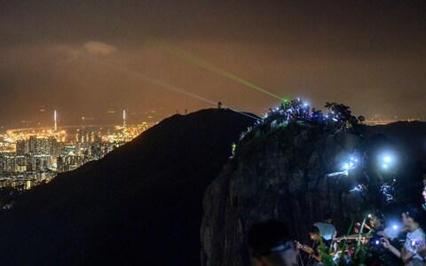 <span>People light up laser beams at the hill top of Lion Rock in Hong Kong </span> <span>Credit: AFP </span>