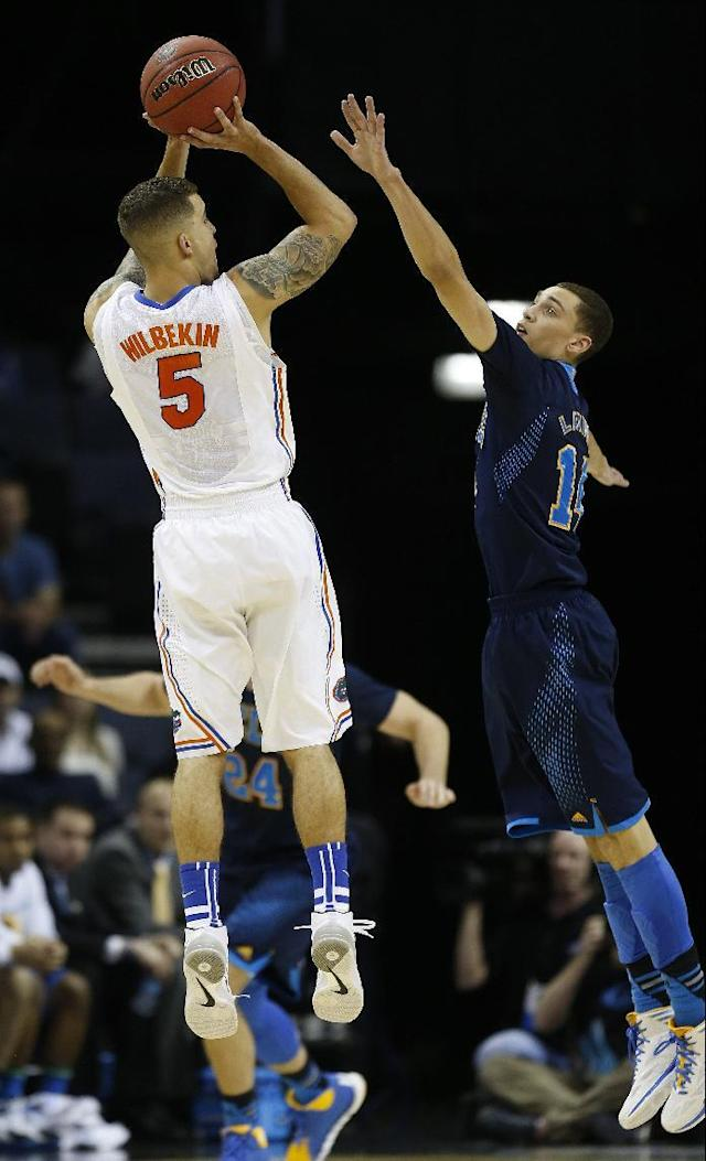 Florida guard Scottie Wilbekin (5) shoots a three-point shot over UCLA guard Zach LaVine (14) during the first half in a regional semifinal game at the NCAA college basketball tournament, Thursday, March 27, 2014, in Memphis, Tenn. (AP Photo/John Bazemore)