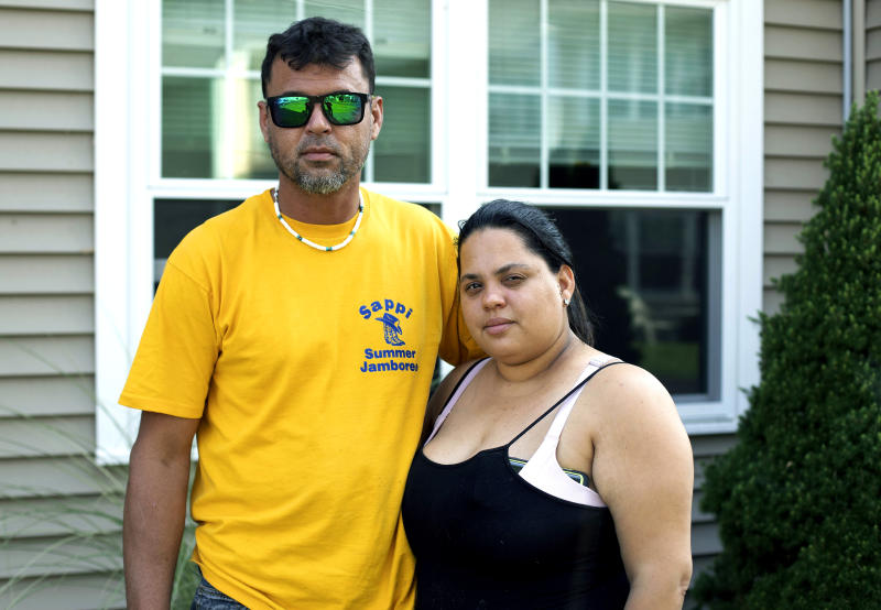 In this Aug. 2, 2019 photo, Ashlyn Gonzales, right, and her longtime partner Emanuel Rivera pose outside their condo in Portland, Conn. In the months after Hurricane Maria destroyed their home in Puerto Rico, the couple moved to Connecticut, where federal and state aid helped them avoid homelessness. But aid at both levels has just about dried up, leaving the pair and many like them wondering what they are going to do next.  (AP Photo/Chris Ehrmann)