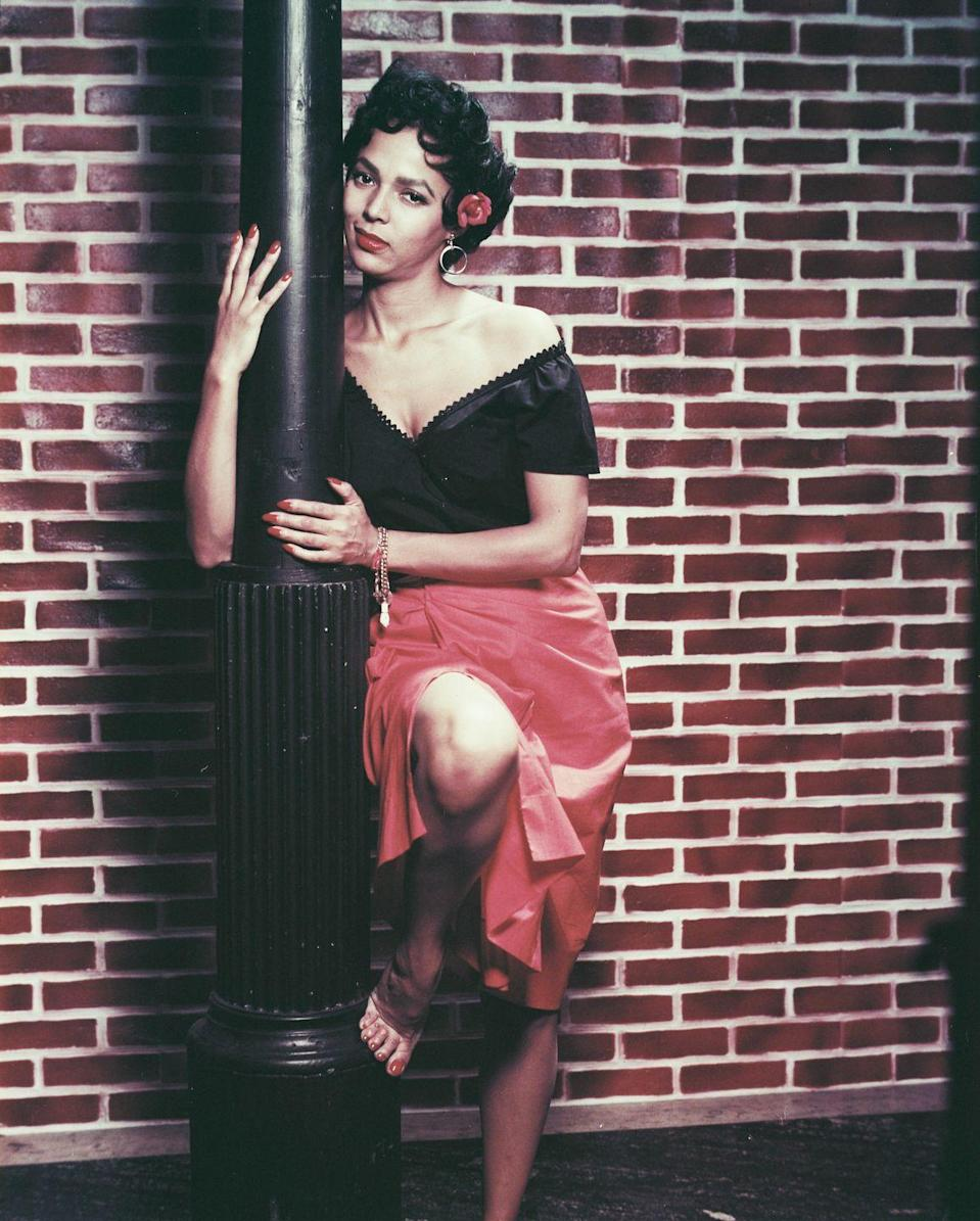 <p>Dandridge's iconic costume for her role in <em>Carmen Jones </em>featured a black off-the-shoulder top, a bright red wrap skirt, and gold hoop earrings.</p>