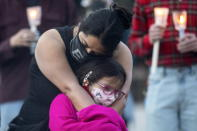 A mother hugs her daughter during a vigil in Toronto on Sunday May 30, 2021, for the 215 Indigenous children, whose remains were uncovered on the grounds of a former residential school near Kamloops, British Columbia. The discovery of a mass grave was announced late on Thursday by the Tk'emlups te Secwépemc people after the site was examined by a team using ground-penetrating radar. (Chris Young/The Canadian Press via AP)