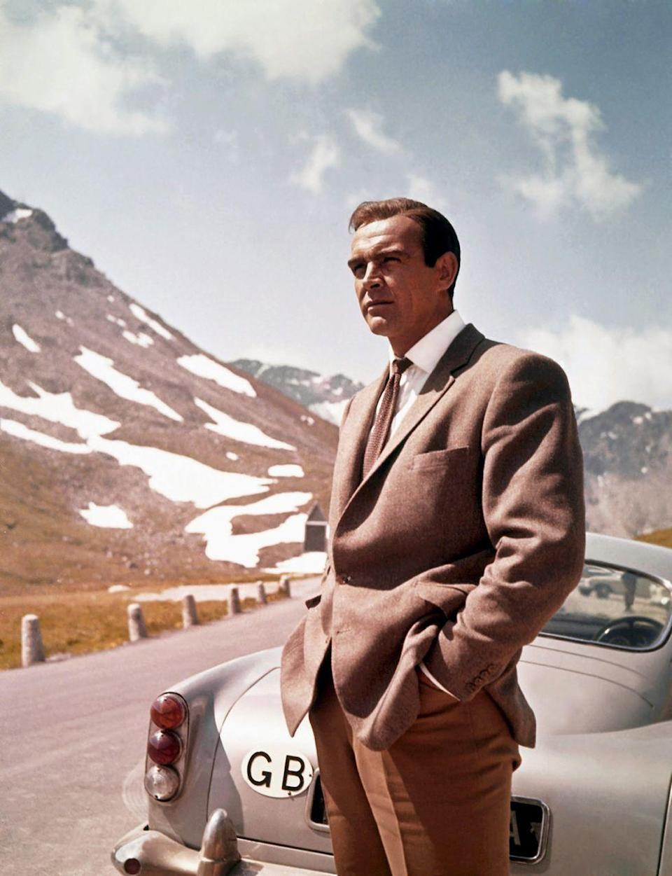 <p>Next to his Aston Martin DB5 in a scene from <em>Goldfinger</em>. </p>