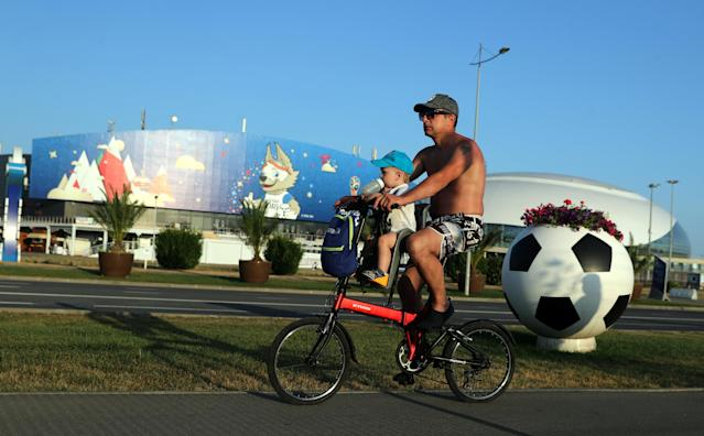 A man and a child ride a bicycle near Fisht Stadium in Sochi, Russia June 17, 2018. REUTERS/Marcos Brindicci