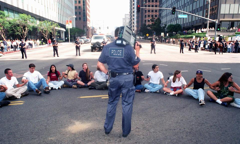 A Los Angeles Police Department official videotapes a rally to protest the University of California regents' decision to scrap affirmative action policies, on Oct. 12, 1995, in Los Angeles. (Chris Pizzello / AP file)