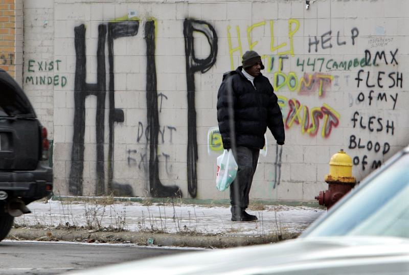FILE - A pedestrian walks by graffiti in downtown Detroit in a Dec. 12, 2008, file photo. Detroit became the largest city in U.S. history to file for bankruptcy on Thursday, July 18, 2013, when state-appointed emergency manager Kevyn Orr asked a federal judge for municipal bankruptcy protection. (AP Photo/Carlos Osorio, File)