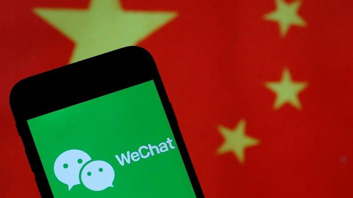 In this photo illustration the logo of Chinese media app for creating and sharing short videos WeChat is displayed on the screen of a smartphone in front of a Chinese flag