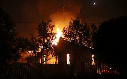 A house burns in the town of Mati, east of Athens - Credit: AP