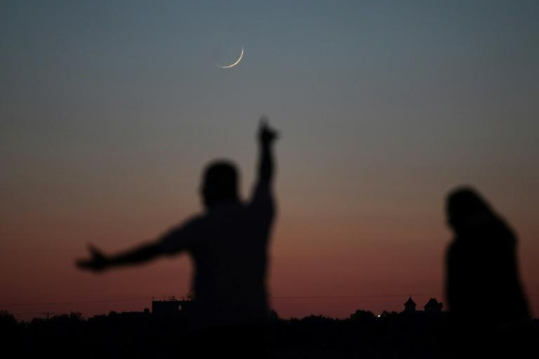 A Palestinian man points towards the crescent moon in Khan Yunis in the southern Gaza Strip on May 16, 2018, a day before the start of the Muslim holy month of Ramadan