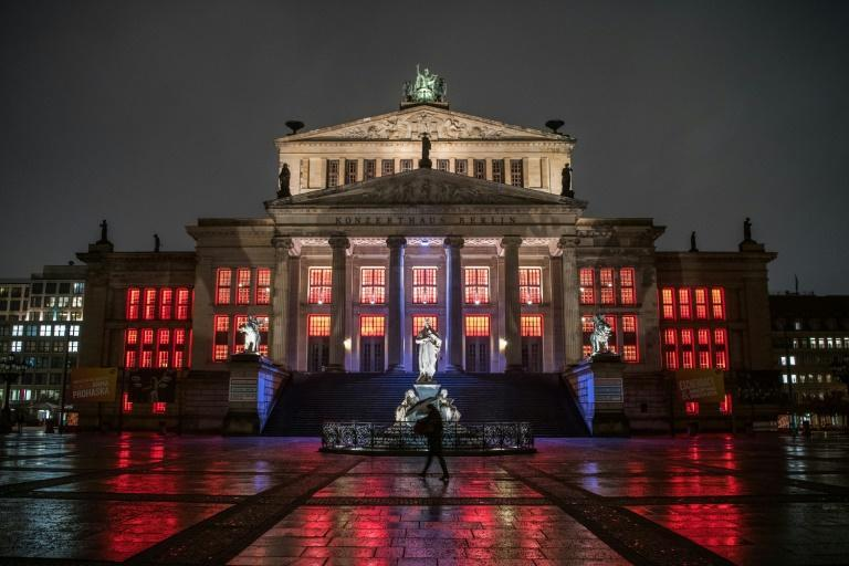 A lone pedestrian walks past the concert hall at Gendarmenmarkt illuminated in red to draw attention to the plight of cultural institutions in Berlin amid the pandemic