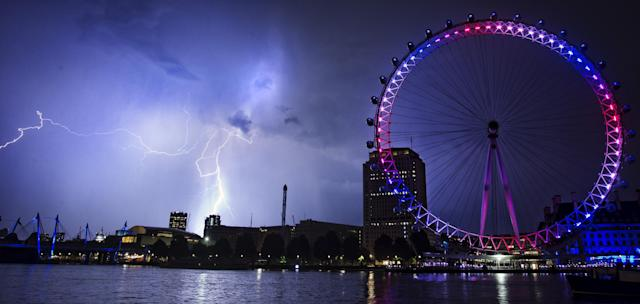 Lightning strikes behind The London Eye in central London which is coloured red, white and blue to mark the birth of a baby boy, at 4.24pm yesterday to the Duke and Duchess of Cambridge at St Mary's Hospital.
