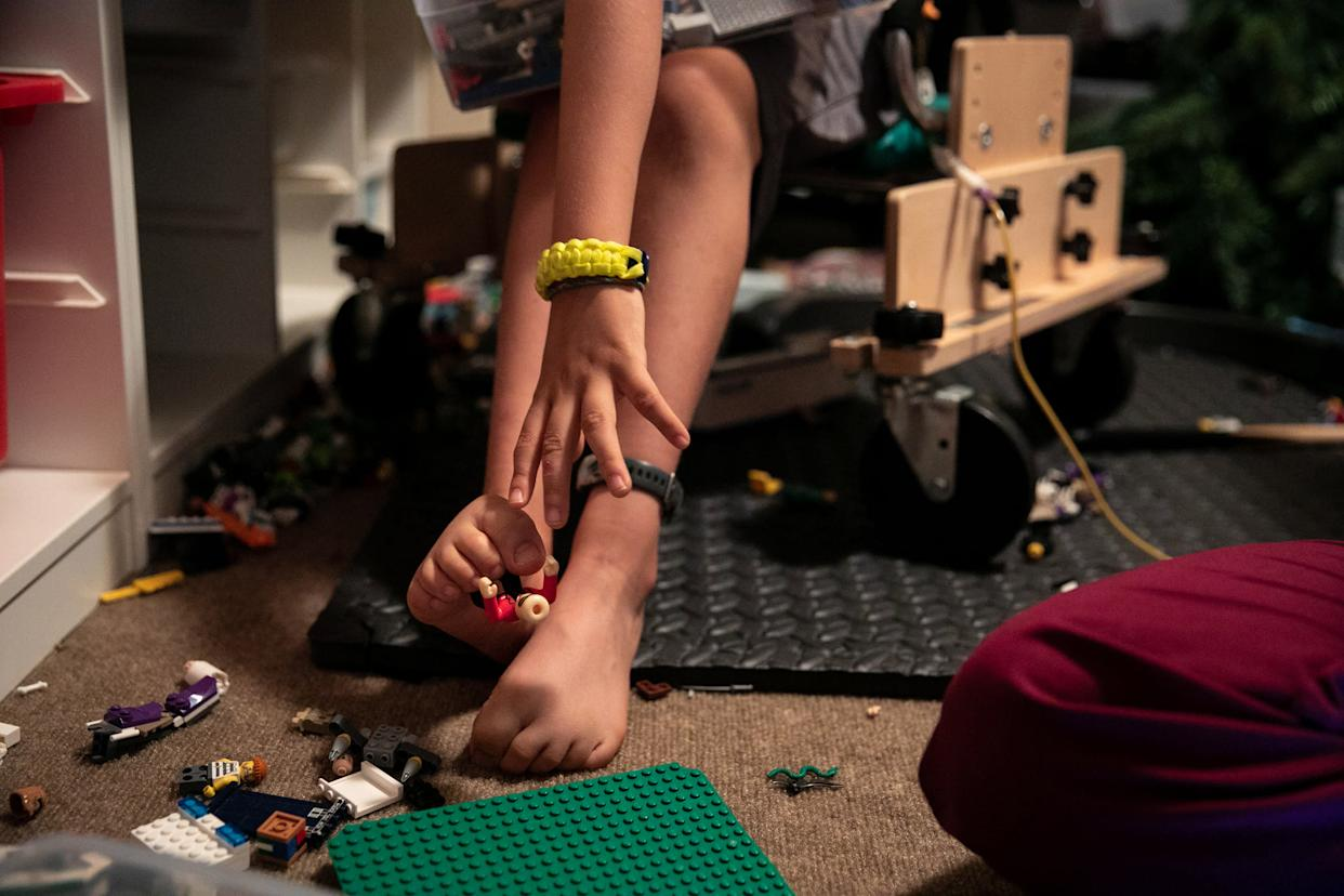 Braden uses his toes to reach for a LEGO on a break inbetween physical therapy treatments. | Ilana Panich-Linsman for TIME