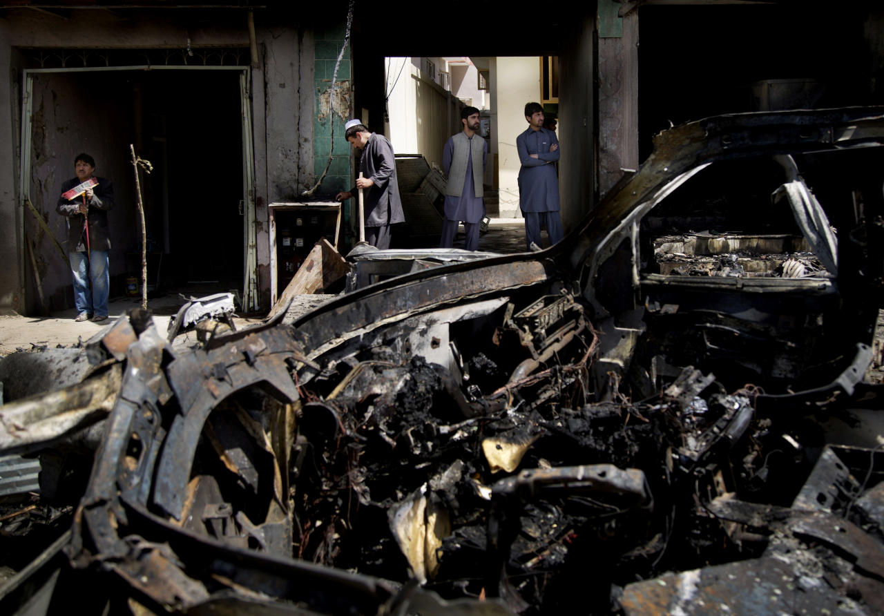 Afghan men clean up the debris after a suicide car bomber attacked a NATO convoy in Kabul, Afghanistan, Thursday, May 16, 2013. A Muslim militant group, Hizb-e-Islami, claimed responsibility for the early morning attack, killing many in the explosion and wounding tens, police and hospital officials said. The powerful explosion rattled buildings on the other side of Kabul and sent a pillar of white smoke into the sky in the city's east. (AP Photo/Anja Niedringhaus)