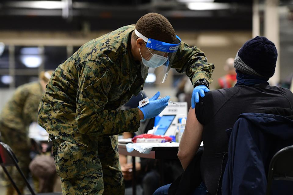 A member of the U.S. Armed Forces administers a dose of the Pfizer COVID-19 vaccine
