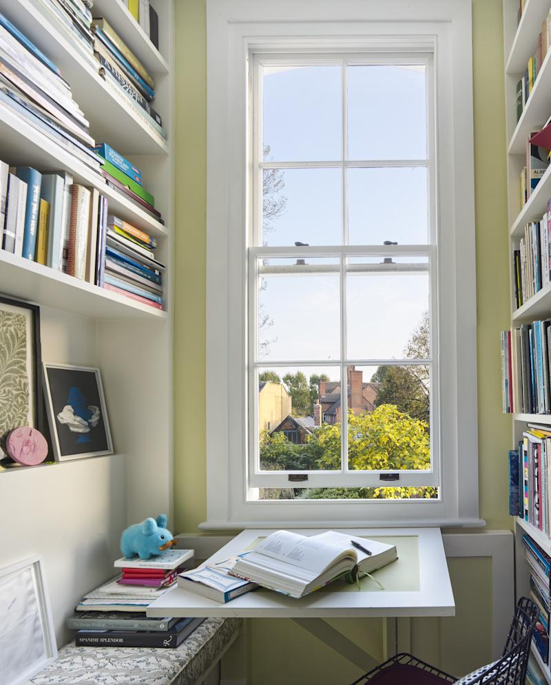 Irwin opted for a Georgian-style celery green in this library niche, where the couple come to browse their collection of architecture and travel books at the foldaway desk. A fragment of the water-damaged William Morris wallpaper that once lined the hallway has been preserved in a frame, maintaining a link with the house's rich history.