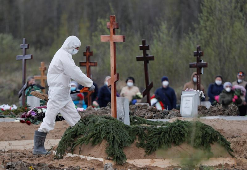 Mourners wear face masks at a cemetery