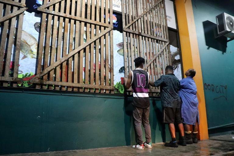 People secure their shop with wooden planks ahead of the arrival of super Cyclone Yasa in Fiji's capital city of Suva