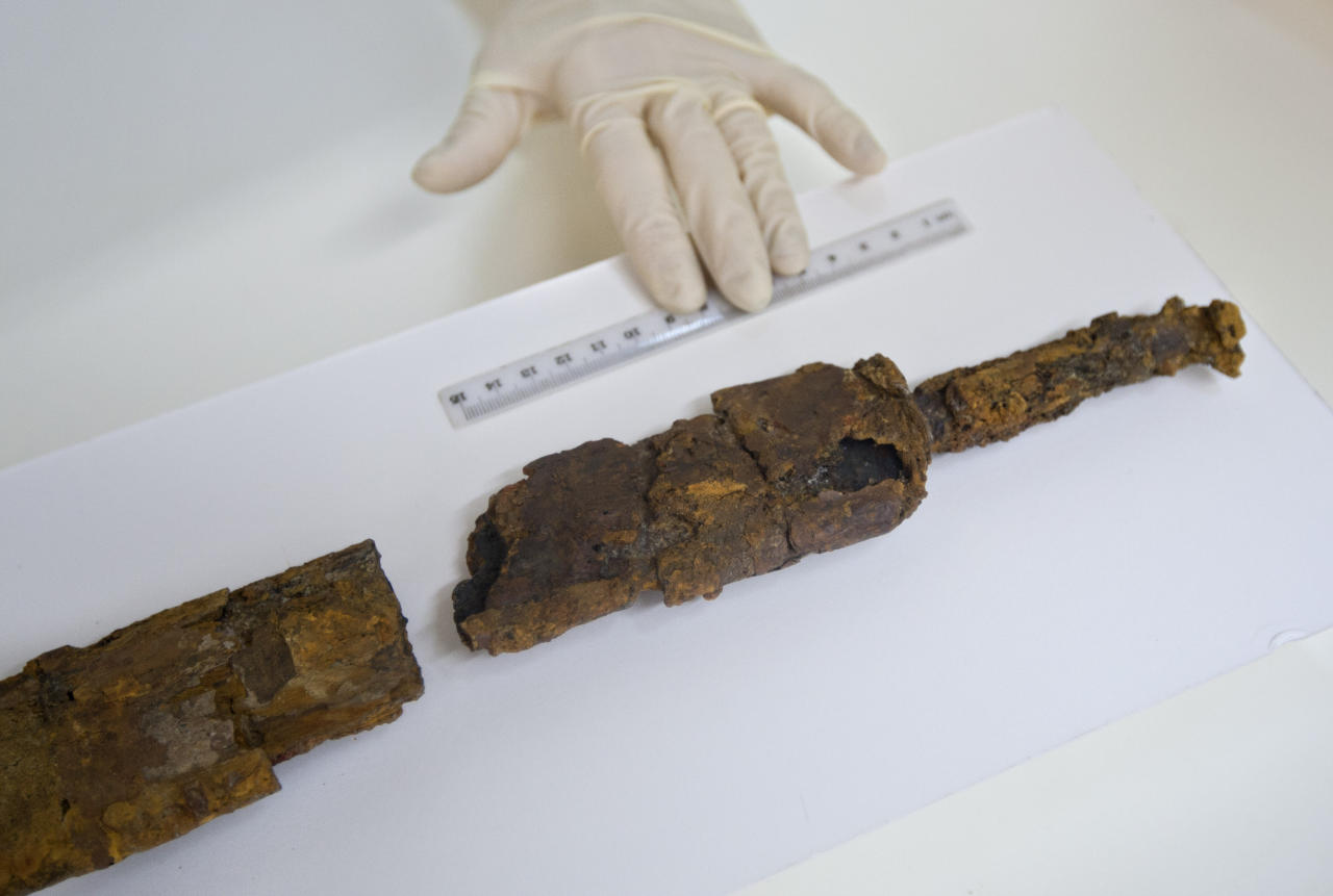 A worker with the Israel's Antiquities Authority shows a sword found in what archaeologists say is a 2,000-year-old drainage tunnel leading to Jerusalem's Old City, at the IAA's offices in Jerusalem, Monday, Aug. 8, 2011. On Monday, archaeologists from the IAA unveiled a standard-issue Roman legionnaire's sword found during excavations of an ancient drainage tunnel beneath Jerusalem, late last month. The excavation of the tunnel has yielded new artifacts from a war here 2,000 years ago, archaeologists said Monday, shedding light on a key episode of the past buried under today's politically combustible city. (AP Photo/Sebastian Scheiner)