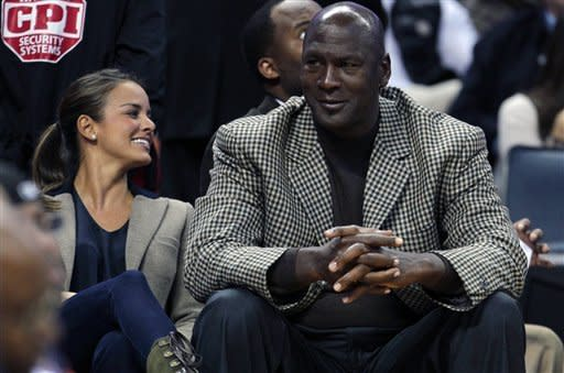 Charlotte Bobcats owner Michael Jordan, right, sits with his fiancee, Yvette Prieto, left, during the first half of an NBA basketball game between the Charlotte Bobcats and the Golden State Warriors in Charlotte, N.C., Saturday, Jan. 14, 2012. (AP Photo/Chuck Burton)