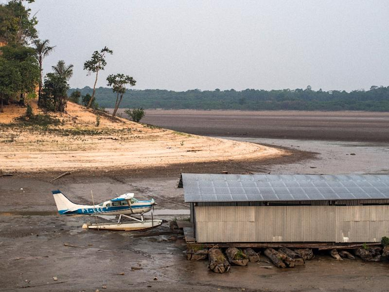 A stranded amphibious aircraft is seen next to a hangar on the bed of the Aleixo Lake, in the rural area of Manaus, Amazonas, Brazil, on October 23, 2015 (AFP Photo/Raphael Alves)