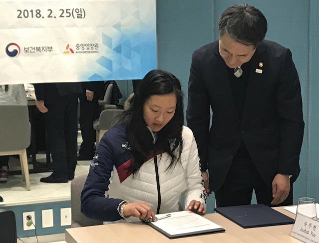 Marissa Brandt signs a proclamation naming her an honorary ambassador for adoptee birth family searches by Neunghoo Park, right, South Korean minister of health and welfare, during a lunch in Gangneung, South Korea. Brandt, adopted as a baby by Greg and Robin Brandt of Vadnais Heights, Minnesota, played for South Koreas historic combined womens team under her birth name, Park Yoonjung. (AP Photo/Teresa M. Walker)