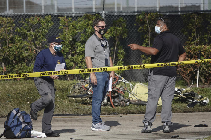 NTSB investigators work the scene of a Monday plane crash near North Perry Airport in Pembroke Pines, Tuesday, March 16, 2021. A four-year-old child riding in a vehicle on the ground and the pilot and passenger in the plane were killed. (Joe Cavaretta/South Florida Sun-Sentinel via AP)