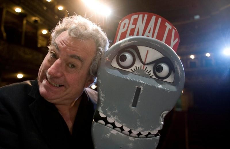 """FILE PHOTO: Former Monty Python Jones poses next to """"the parking meter from hell"""" before an interview with Reuters in Lisbon"""