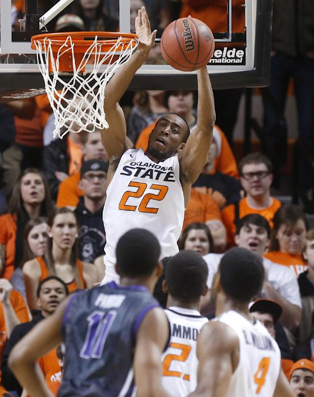 Oklahoma State wing Markel Brown (22) grabs a pass at the basket in front of TCU forward Brandon Parrish (11) and Oklahoma State's Leyton Hammonds (23) and Brian Williams (4) during the first half of an NCAA college basketball game in Stillwater, Okla., Wednesday, Jan. 15, 2014. Oklahoma State won 82-50. (AP Photo/Sue Ogrocki)