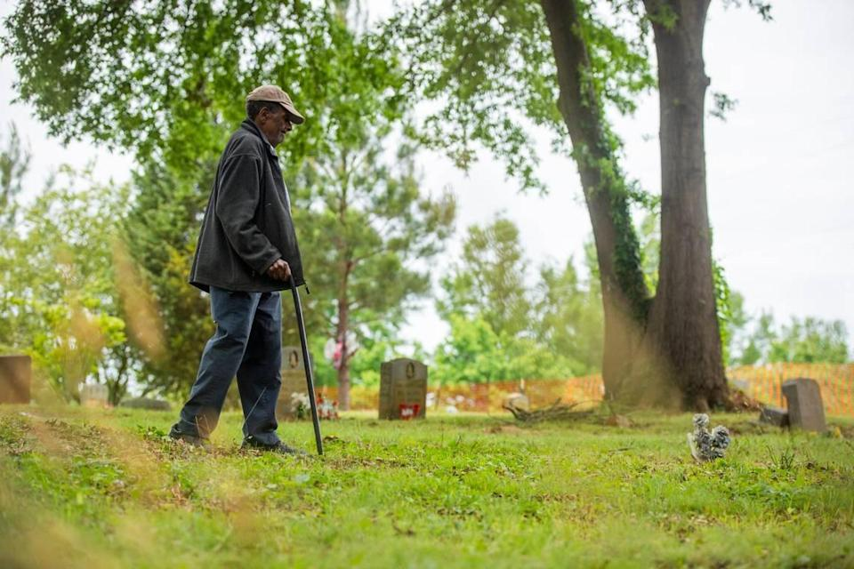 Former caretaker Rudolph Loftin Sr., now 97, walks with his cane through the Oak Grove Cemetery, which was founded by freed African-Americans after the Civil War and now has lost more of its tree buffer to widening of the I-440 Beltline, that separated it from the rest of the Method community in the 1960s, on Tuesday, May 11, 2021, in Raleigh, N.C.