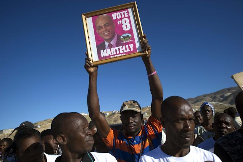 Supporters of Haitian President Michel Martelly wave a sign as Martelly addresses a crowd during a memorial ceremony on January 12, 2015 in Titanyen, in honor of the victims of earthquake that hit Haiti in January 12, 2010 (AFP Photo/Hector Retamal)